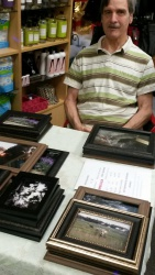 Artist Jim Ferris, sits behind his photography offered for sale at local art fairs in and around Wisconsin.